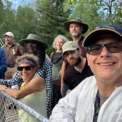 Un homme souriant, à l'avant plan d'un groupe de sept personnes, à l'extérieur. Deux d'entre eux portent un filet au visage, contre les moustiques.