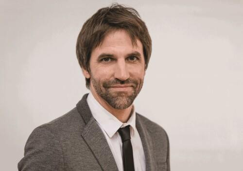 Steven Guilbeault vêtu d'une veste grise et cravate noire sur chemise blanche.