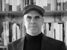 Homme avec casquette, chandail et gilet noir en avant d'une bibliothèque.