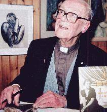 Homme prêtre âgé avec lunettes, gilet et chemise brune assis à un bureau avec plume à la main.