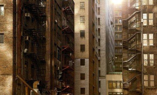Façades d'immeuble en pierre de nuances beige à marron selon la lumière avec escalier extérieurs. Les nombreuses fenêtres laissent penser qu'il y a beaucoup d'appartements.