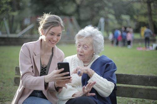 Jeune femme assis sur un banc dans un parc avec dame âgée aux cheveux blancs regardant photo dans un téléphone intelligent.