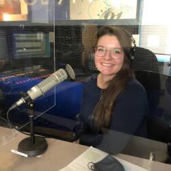 Josée est assise dans le studio de la radio devant un micro en portant des écouteurs. Elle porte un chandail bleu foncé à manche longue.
