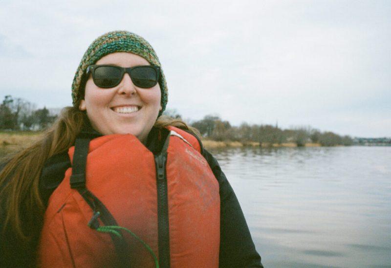 Femme portant un gilet de sauvetage orange, assise dans un bateau sur un lac.