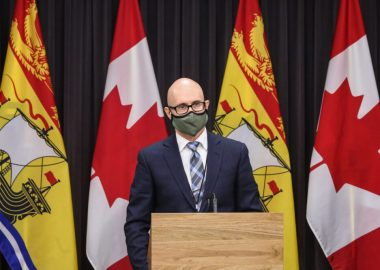 Dr. Dow stands behind a podium and is wearing a mask.