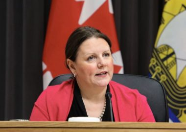 Jennifer Russell sits at a wooden podium at a press converence with a Canada flag and New Brunswick flag behind her.