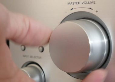 A hand turning the volume dial lower.