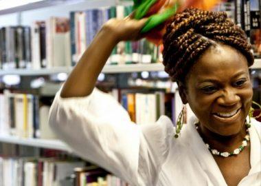 Joujou Turenne, blouse blanche, collier, tresses africaines, tout sourire, foulard au vent