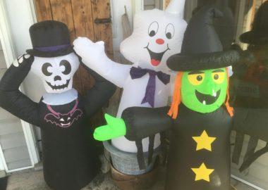 Un squelette, un fantôme et une sorcière gonflable en face d'un magasin comme décorations pour l'Halloween