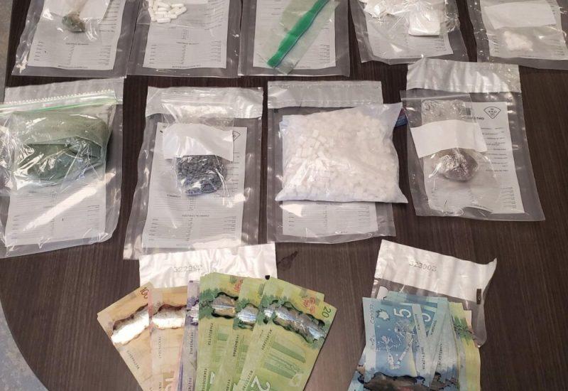 Plusieurs sacs de drogues et de l'argent étalés sur une table