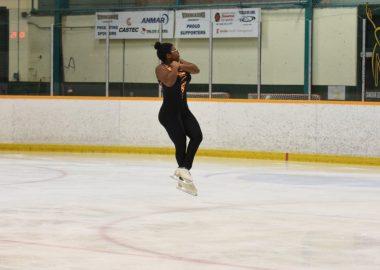 Une jeune patineuse qui fait une figure dans les airs sur la patinoire