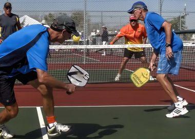 4 personnes jouent au Picleball, 2 personnes de chaque coté d'un filet, ils sont en plein action, ils ont des tenues de sport et des raquettes plus petite que des raquettes de tennis. Le temps est beau et ils sont concentrés.