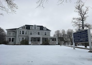 Historic white and grey mansion on a winter day.