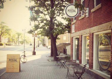 Le café postal vu de dehors, deux tables avec des chaises longe le long du mur avec une enseigne dehors qui montre le menu du café.