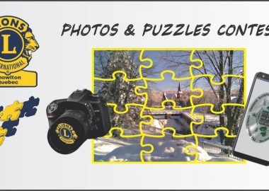The advertisement for the photos and puzzles contest. There is the logo of the Knowlton Lions in the top left corner. There is a puzzle in the middle with a camera to its left and a phone on the right.