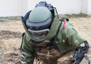 Une personne vêtu d'un uniforme de protection s'approche pour neutraiser une bombe dans un chant