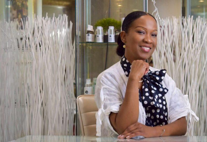 Magalie Avril portant une blouse blanche et un chemisier à boucle sur fond de bambou décoratif et vitrine exposant des produits de soin.
