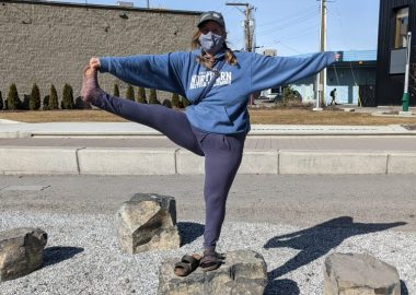 Cynthia Andal holding a yoga pose on a landscaping rock downtown.