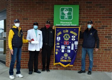Three lions club members and local pharmacist. The lions club banner is k=held up between the people.
