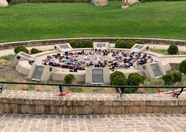 Sur un site circulaire en brique, des centaines de petits souliers sont sur le sol, une colline couverte d'herbe verte derrière la plateforme.