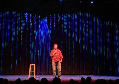 Humoriste avec chemise orange et culottes brunes en spectacle à côté d,un banc et devant une foule.