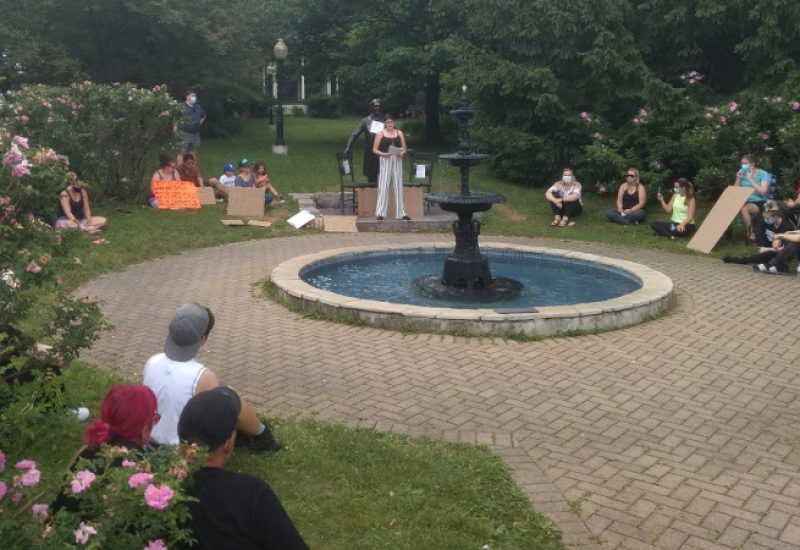 People sitting in the park and listening to Cheyanne Thorpe discuss the negative impacts of the Sir John A MacDonald statue, which stands behind her.