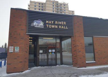 La facade d'un petit édifice brun, ou est inscrit «Hay River Town Hall», avec un immeuble en arrière plan .