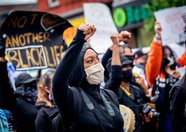 Une femme noire a le poing levé dans une manifestation avec des pancartes contre les actes de racismes.