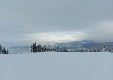 A sky view from the top of a ski mountain in Smithers BC. The sun is just breaking through the sky which is otherwise mostly clouds.