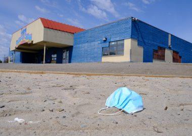 Un couvre visage bleu est sur le sol, devant une école