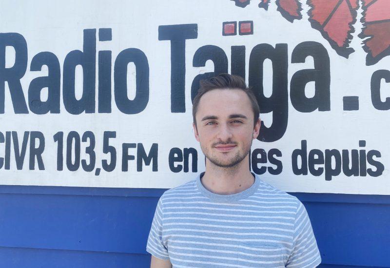 Damian Benoit vêtu d'un chandail rayé, devant une pancarte du logo de radio Taïga.