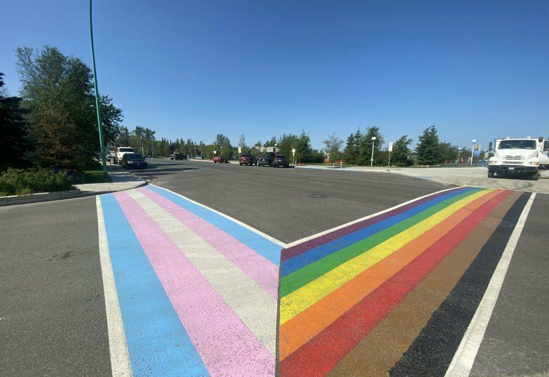 Deux traverses piétonnes se joignent, l'une aux couleurs de l'arc-en-ciel, l'autre bleue, blanc et rose, couleurs du drapeau transgenre.