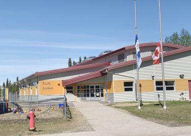 En été, la devanture d'une école. Les drapeaux du Canada et des Territoires du Nord-Ouest sont en berne.