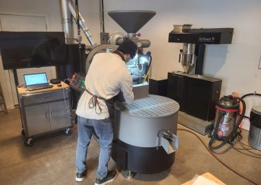 A man is facing a very large coffee bean roaster that he is working to roast beans.
