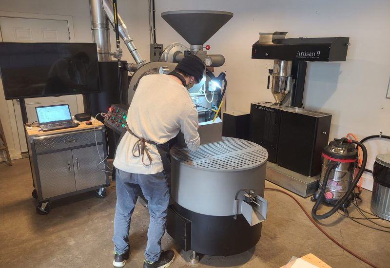 a white man is facing a very large coffee bean roaster that he is working to roast beans.