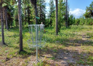 Glen Ingram lines up a 20 foot putt into a disc golf basket at Skillhorn Disc Golf Course in Telkwa, BC.