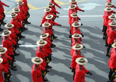 Rows of RCMP, dressed in red coasts and stetsons hats, marching on parademounted poolce
