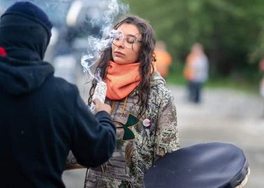 A man wearing black holds up smudging materials that smoke in front of a woman's face in a ceremony at Fairy Creek.