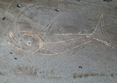A salmon made of driftwood is seen on the grey bank of a river.