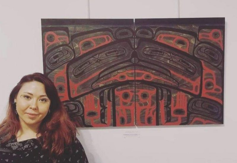 A woman stands next to a red and black Indigenous art work on a wall