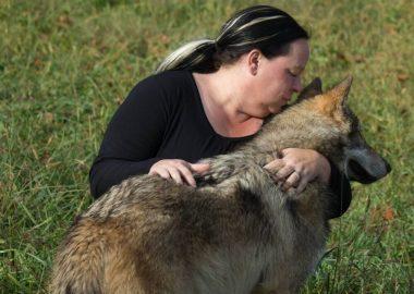 Femme dehors qui flatte un chien.