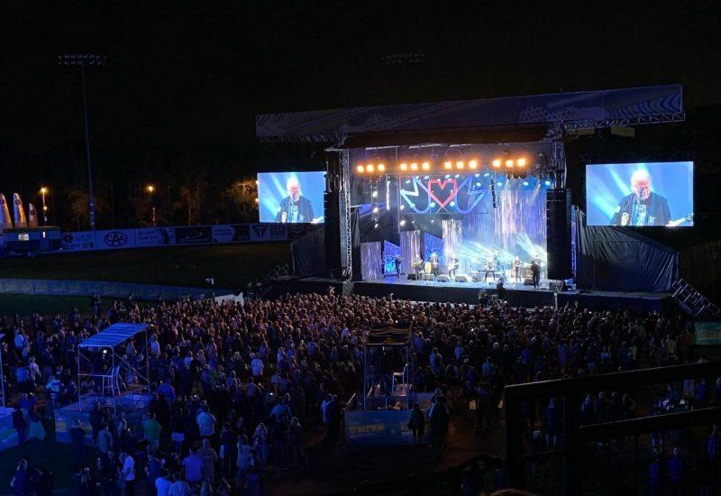 Tard le soir, une grande foule est debout devant un estrade illuminé par les lumières bleues et jaunes.
