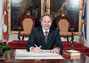 Homme politicien, assis à un bureau, signant des documents.