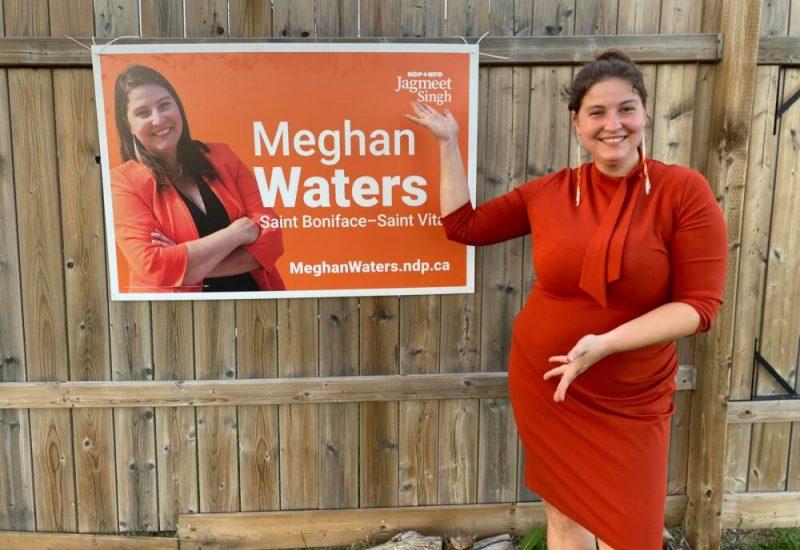 Meghan, souriante et habillée en robe orange, pointe à une pancarte électorale d'elle même accrochée sur une haute clôture en bois.