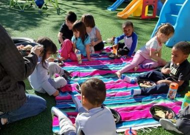 Children sitting and enjoying a picnic outside their early learning centre