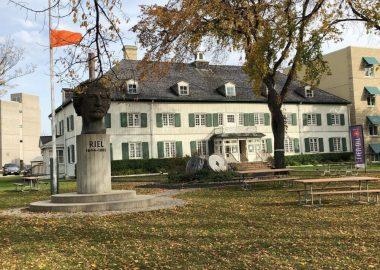 Le musée au mur blanc et fenêtres vertes dans une cours d'herbe pendant l'automne, une statue de Louis Riel devant le musée, et un drapeau orange ballotte au vent à gauche du musée.