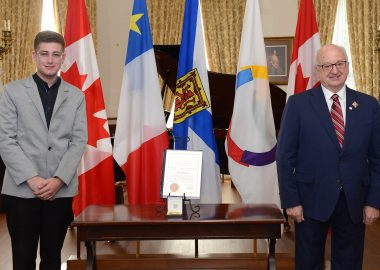 Adrien Comeau a droite, un jeune a lunettes en costume gris pose a coté de la médaille, de l'autre coté, Artur J Leblanc, sourit et pose également, ils sont dans un intérieur richement décoré devant des drapeaux du Canada, de la francophonie, de la nouvelle écosse et de l'Abadie