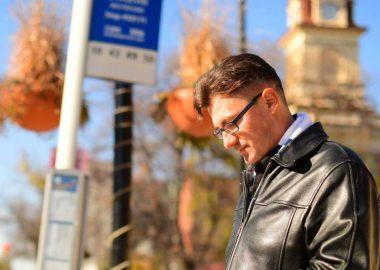 Matt, portant un manteau noir, debout à un arrêt d'autobus.