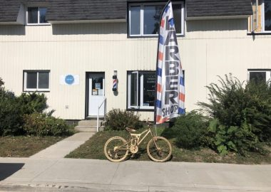 A photo of a children's bicycle, spray painted in gold, sits outside of Sweeny T's Barbershop in Mount Forest.