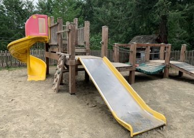 A playground with equipment such as slides and climbing wall.